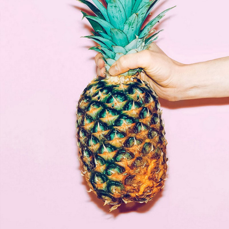girl holding a pineapple on a pink background