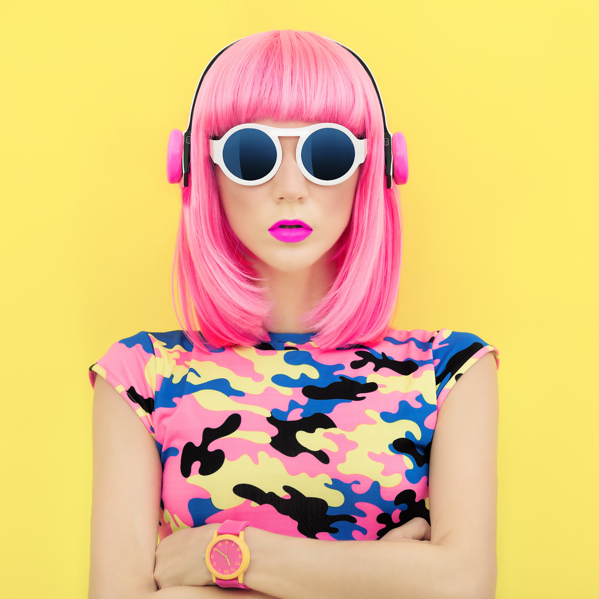 pink haired girl in a military pink top with headphones on yellow background