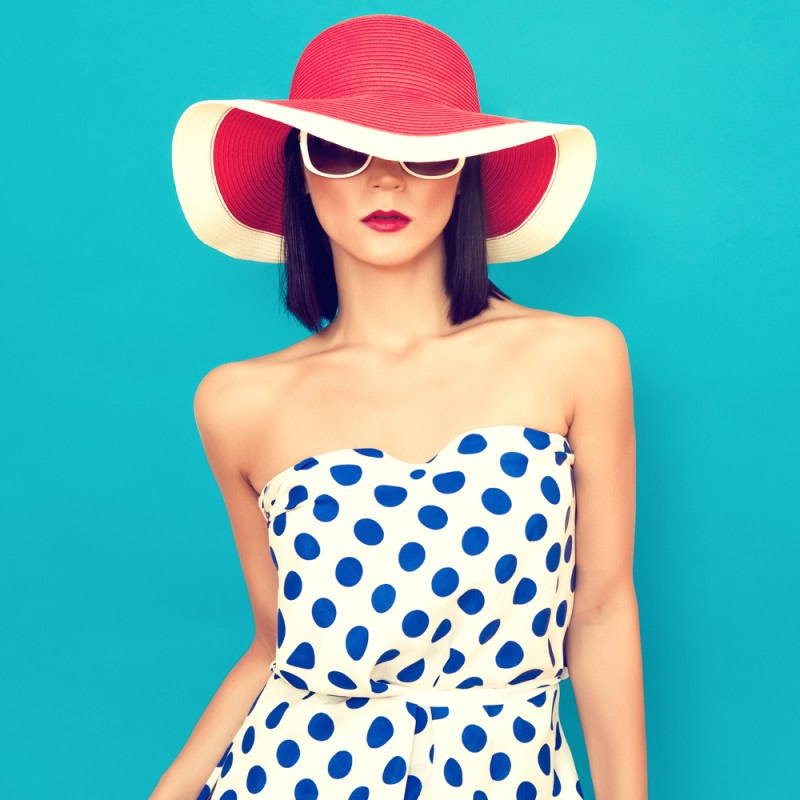 girl in red and white hat and white dress with blue dots on blue background