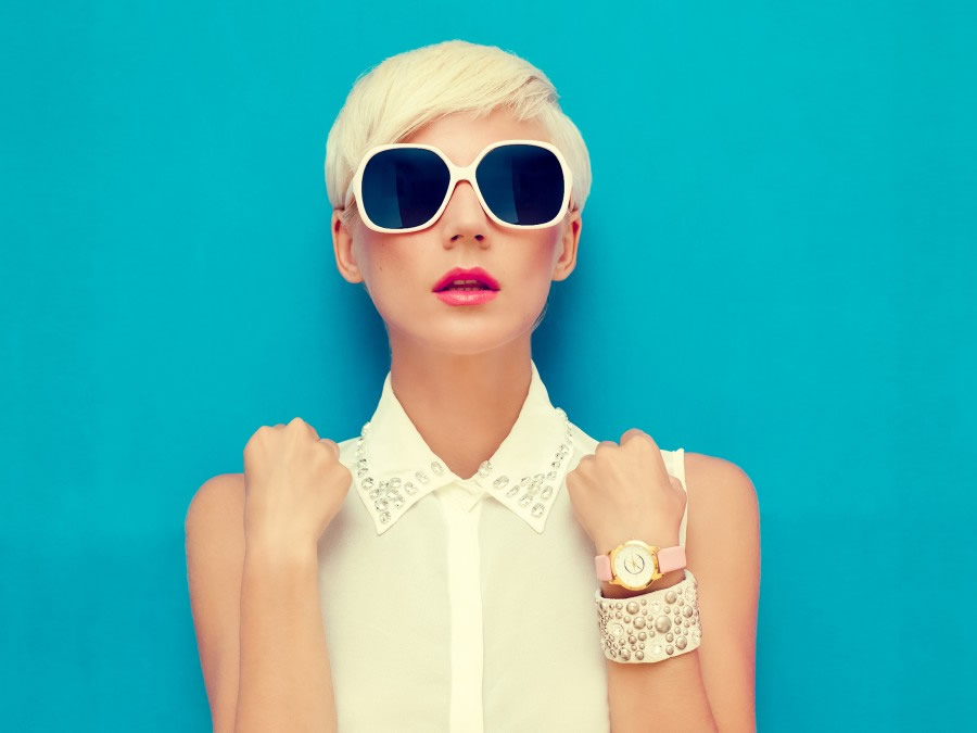 girl in a sleeveless white shirt and sunglasses on blue background