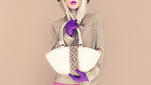 girl in purple hat holding a fashionable handbag on brown background