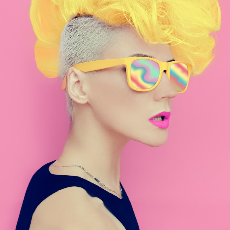 model with yellow haircut and rainbow glasses on pink background