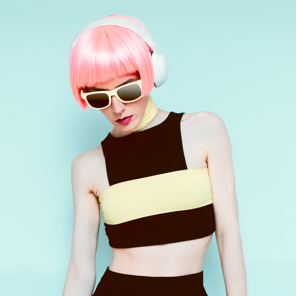 pink haired girl in a fashionable yellow and black top with headphones on mint background