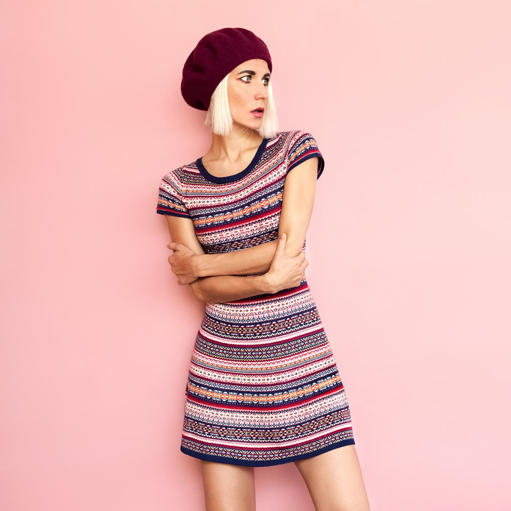 girl in multicolored dress with a scarlet beret on pink pastel background