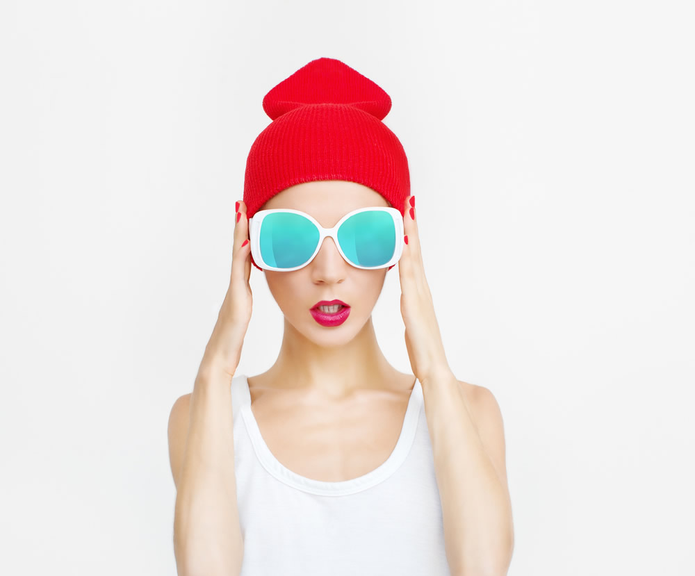 girl in white sleeveless shirt and red hat with blue sunglasses