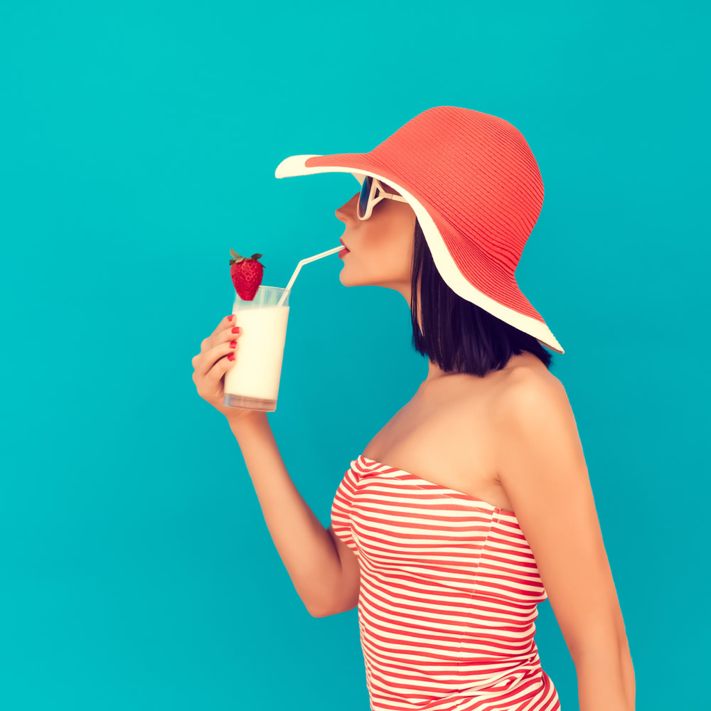 girl with a red hat drinking milk with a strawberry blue background