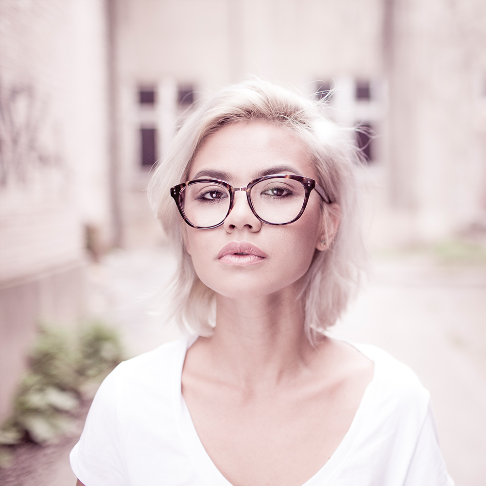 blonde with glasses in a white T-shirt walking the streets