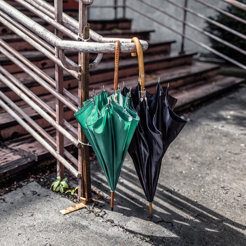 green and black umbrellas at the bottom of an urban staircase