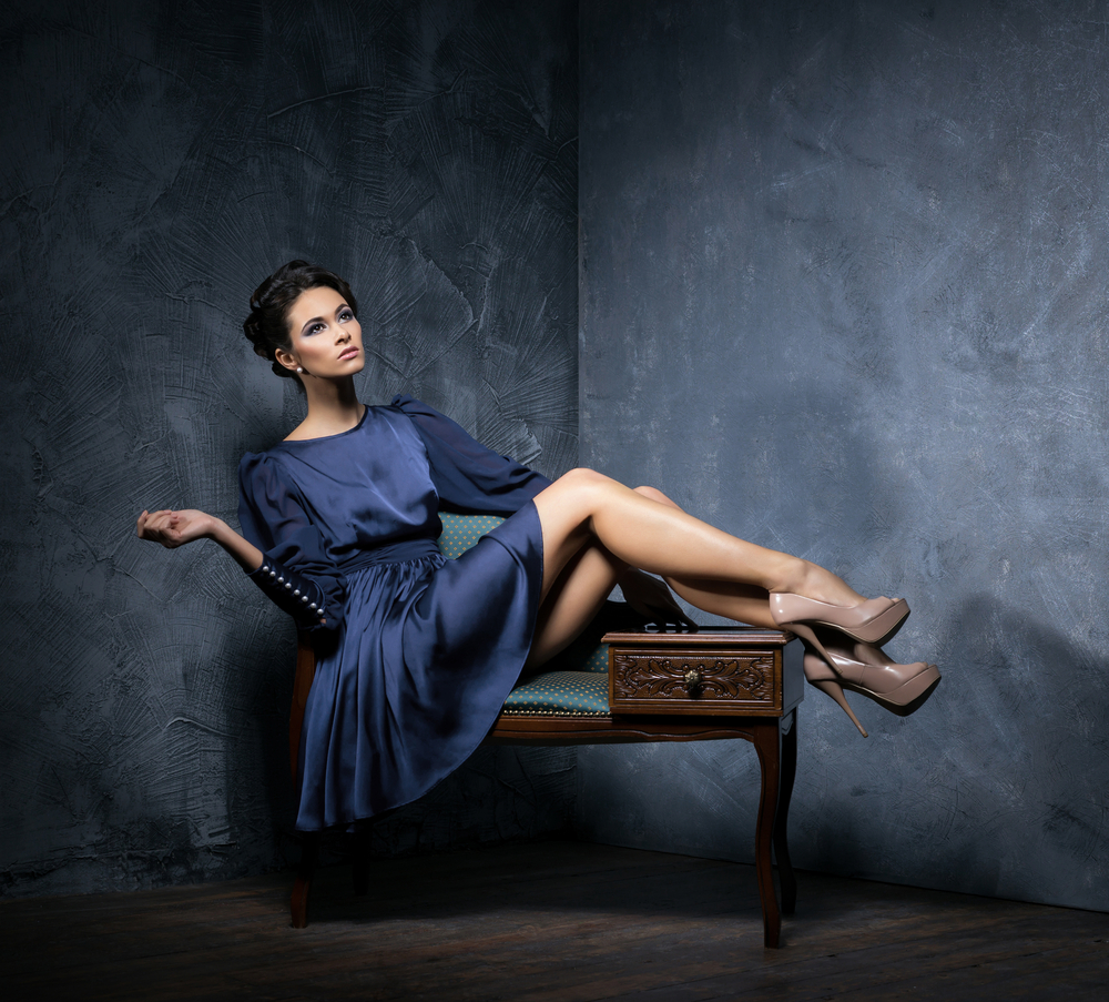 woman in a dark blue dress sitting on a tabouret