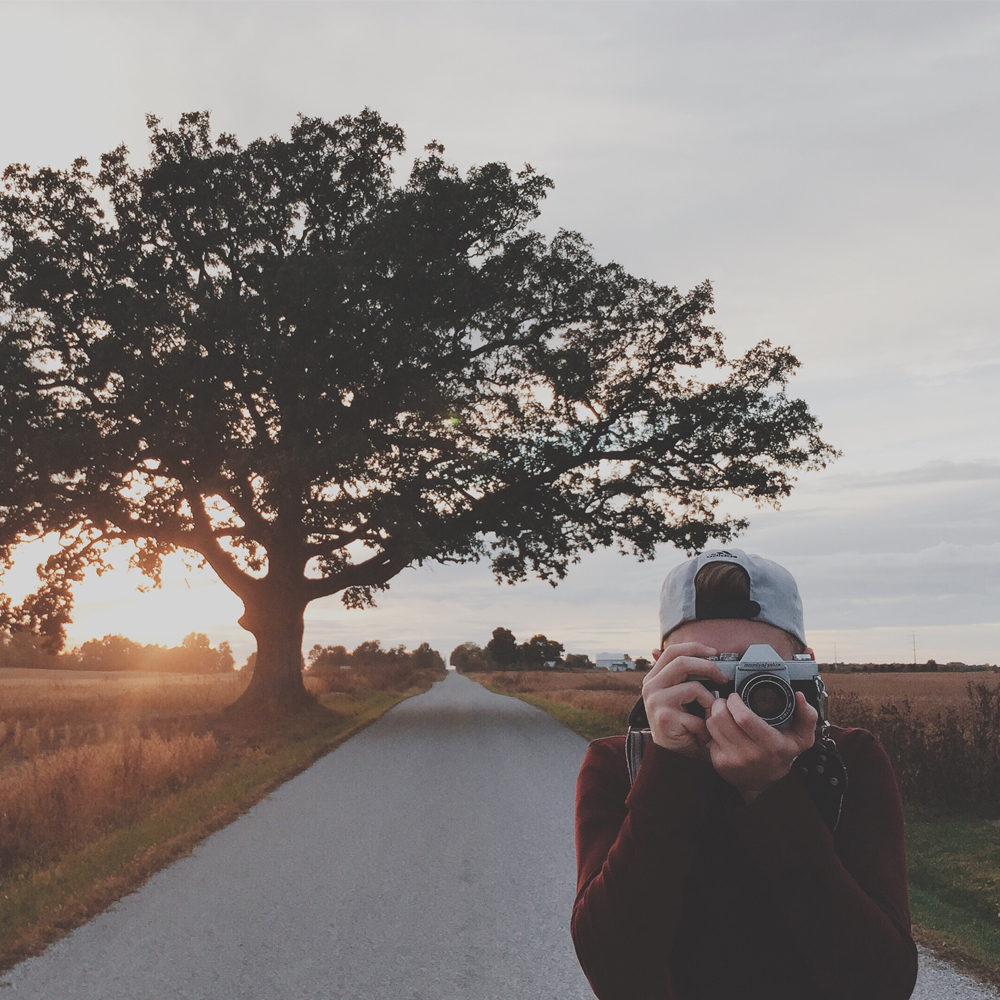 boy taking a picture on a road