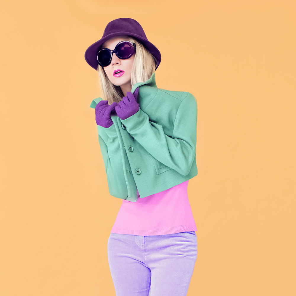 girl in a green coat and purple hat on yellow background