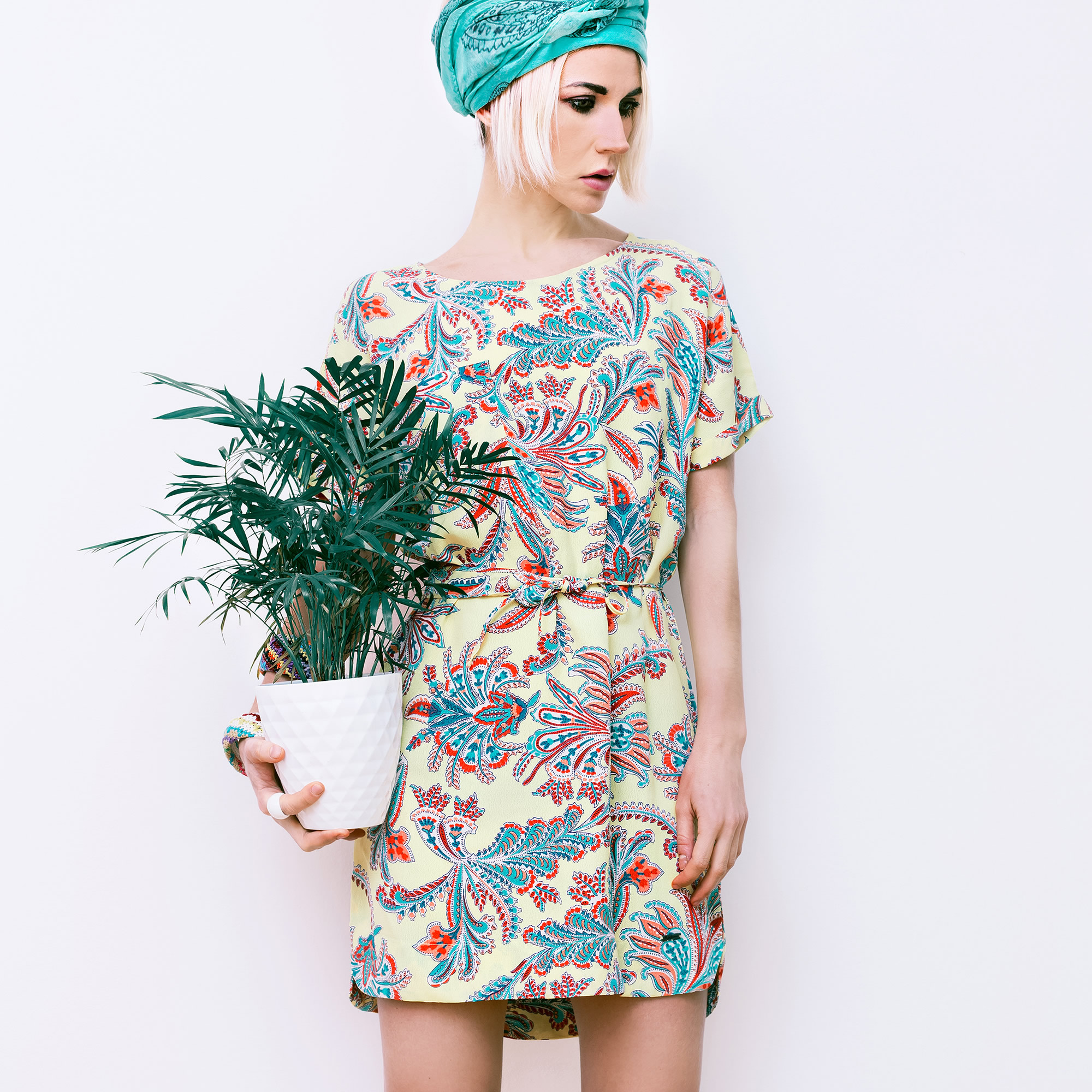 girl in multicolored dress holding a flower in a pot